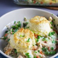 A bowl of chicken and biscuits with peas and carrots