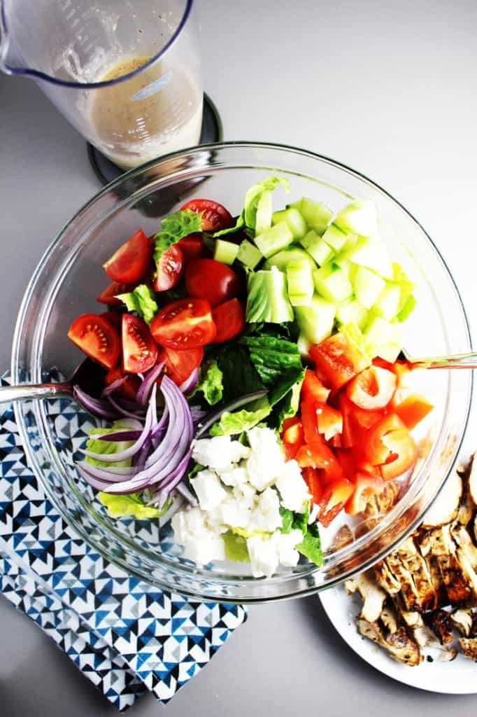 Chopped romaine, tomatoes, onions, cucumbers and red bell peppers in a bowl