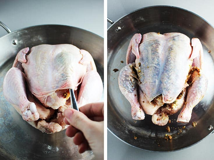 a whole raw chicken in a pan with sun dried tomato pesto being stuffed under the skin with a spoon