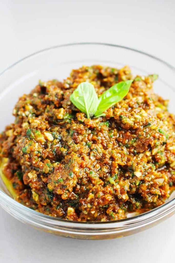 a bowl of sun dried tomato pesto garnished with basil leaves