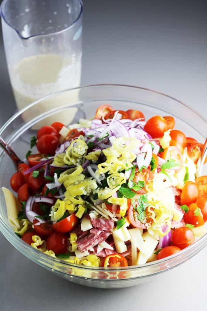 Ingredients for Italian pasta salad in a large salad bowl with prepared dressing in the background