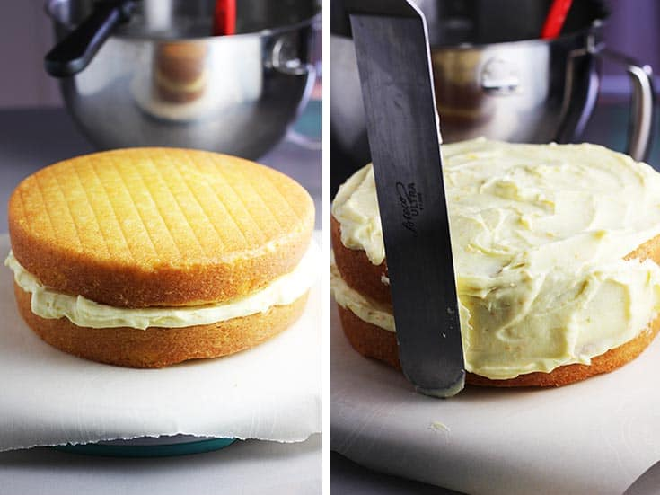 An orange layer cake being frosted with an offset spatula