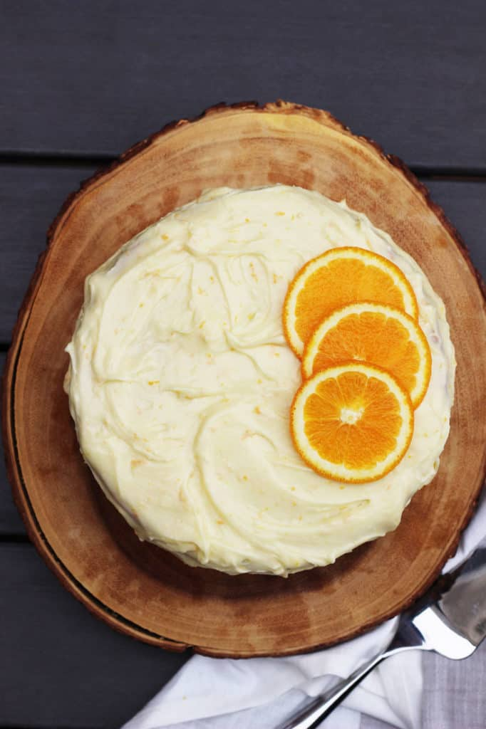 Top view of an orange layer cake with cream cheese frosting garnished with orange slices.