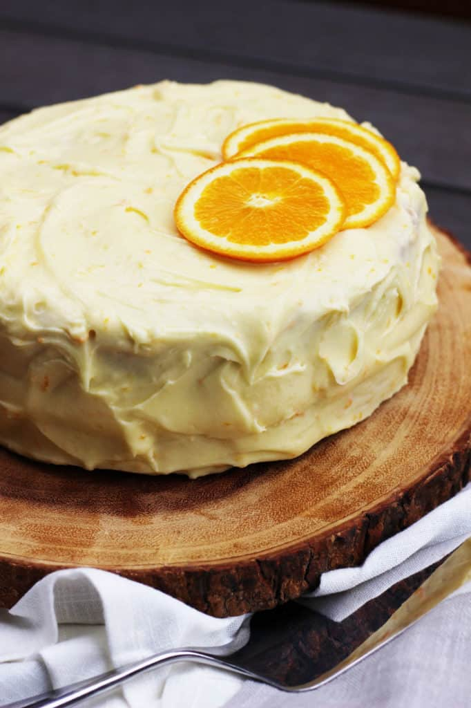 Closeup of a fresh orange layer cake decorated with orange slices on a wooden board