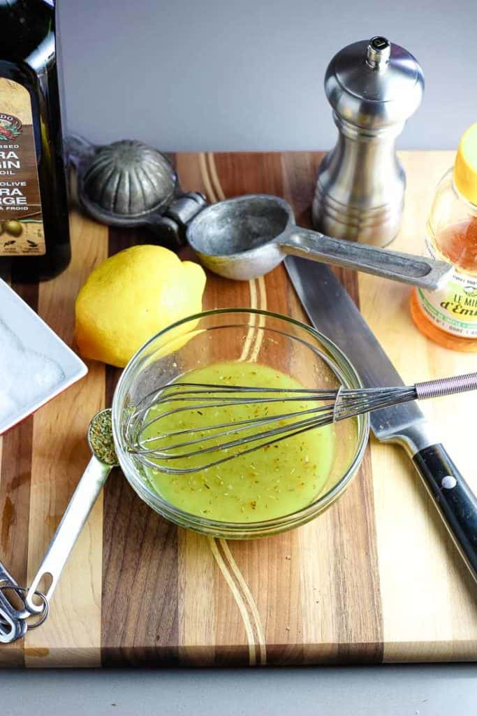 Lemon dressing whisked together in a small glass bowl with ingredients for the dressing all around on a wooden cutting board.