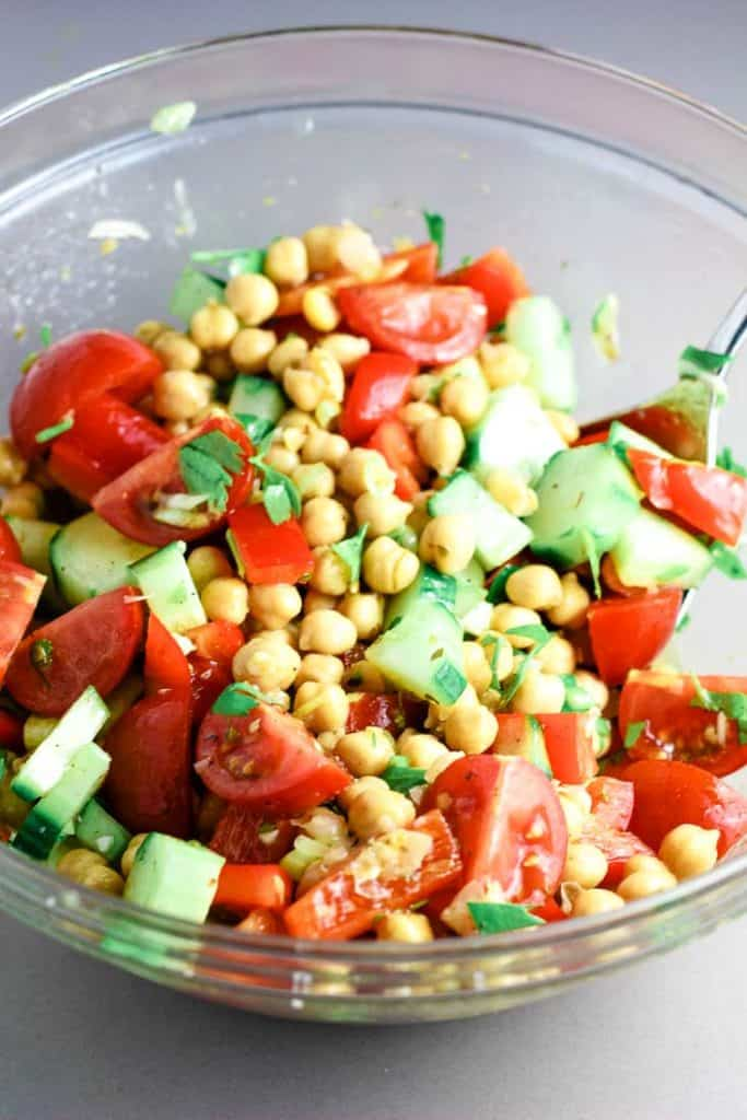 Chopped vegetables and chickpeas tossed with lemon dressing for a Mediterranean Buddha bowl.