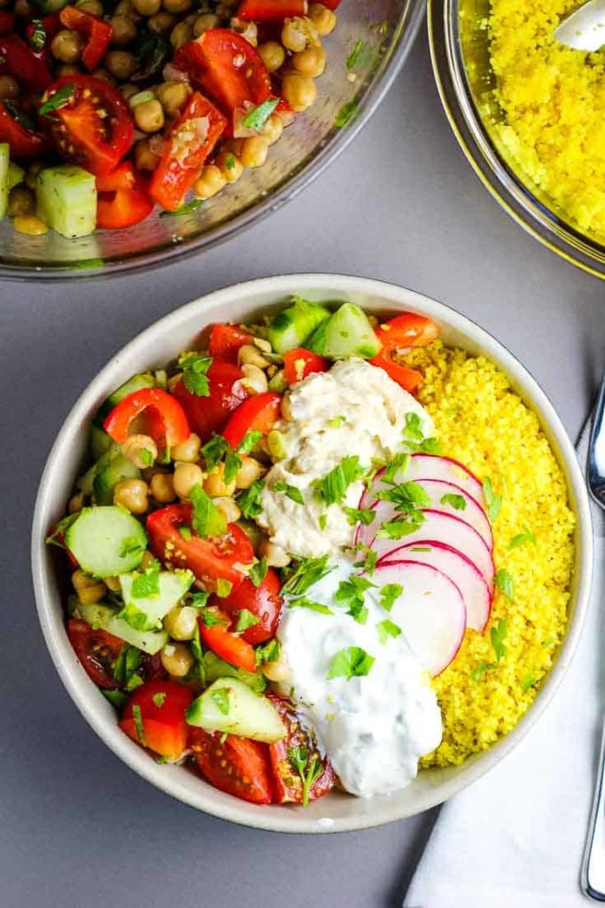 Overhead view of a Mediterranean Buddha bowl with vegetables, couscous, hummus and tzatziki