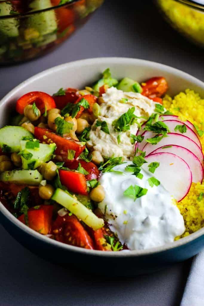 Closeup of a Mediterranean Buddha bowl with couscous, raw vegetables, tzatziki and hummus