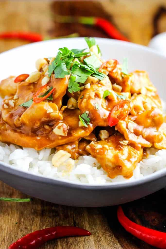 Chicken satay over rice in a bowl garnished with peanuts, cilantro and Thai chiles