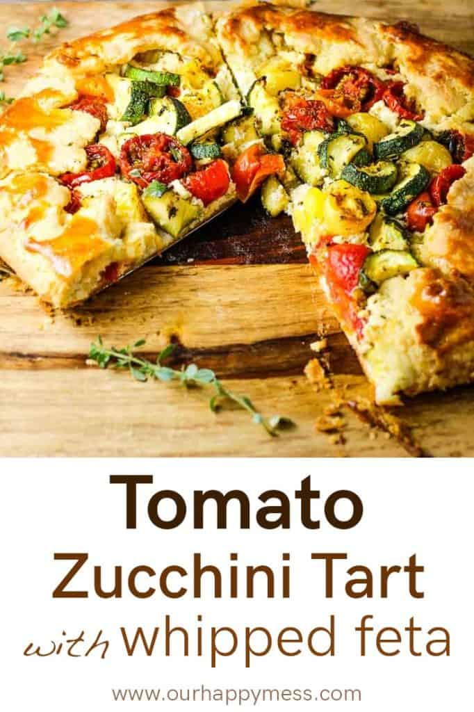 A rustic zucchini tomato tart on a wooden board with a slice taken out