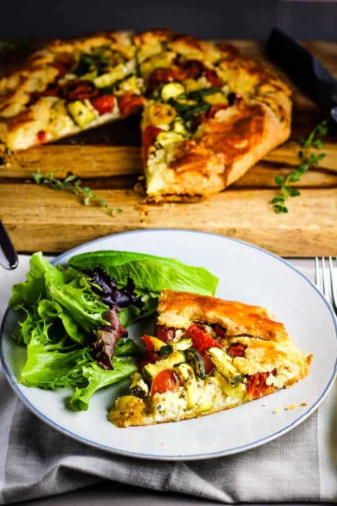 Slice of tomato zucchini tart (galette) on a plate with a green salad