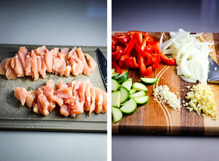 Sliced raw chicken breast on a cutting board and sliced vegetables on a cutting board