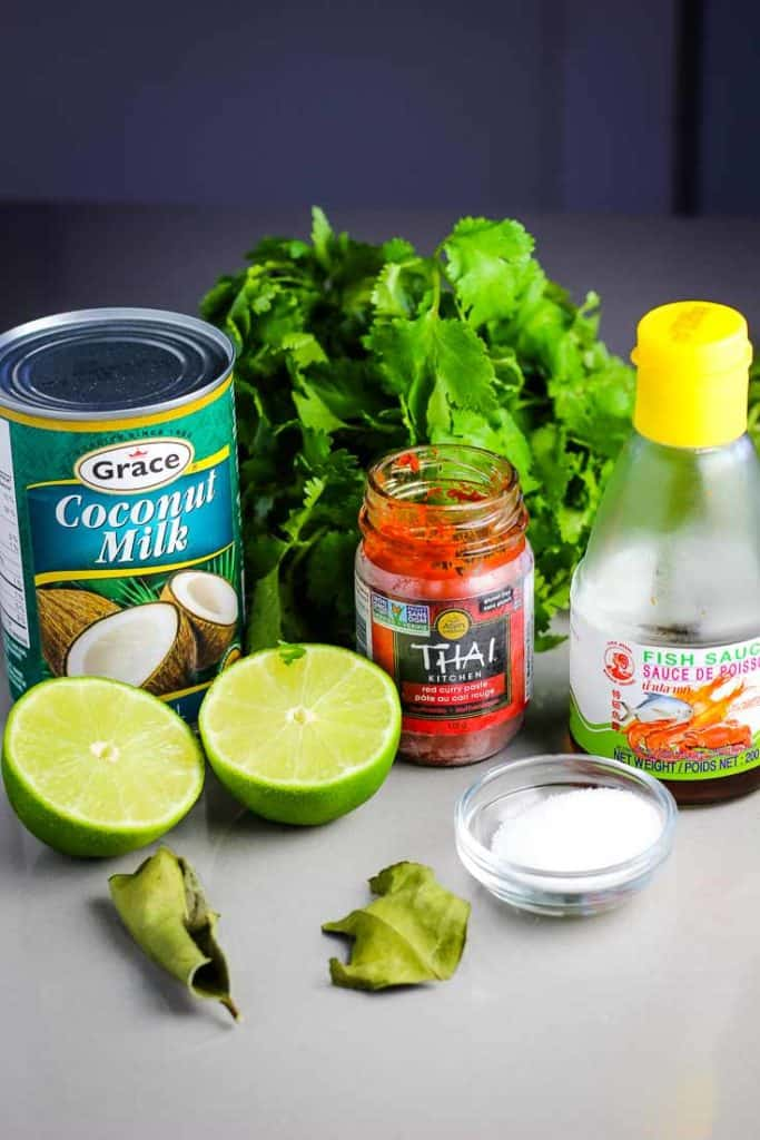 Ingredients to make Thai red curry. Coconut milk, curry paste, fish sauce, cilantro, lime and dried kaffir lime leaves