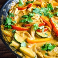 Thai red curry with chicken, rep pepper and zucchini in a pan