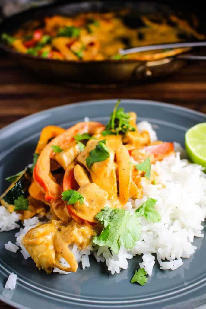 A plate of Thai red curry served over rice with cilantro