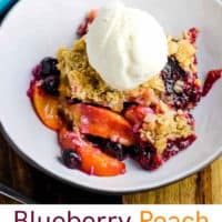 A bowl of blueberry peach crisp with a scoop of vanilla ice cream