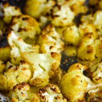 Roasted cauliflower florets on a foil-lined baking sheet
