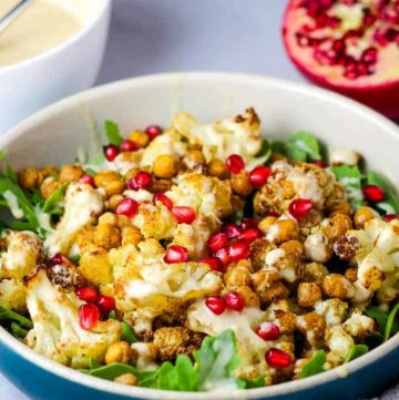 A bowl of roasted cauliflower salad with tahini dressing and pomegranate seeds