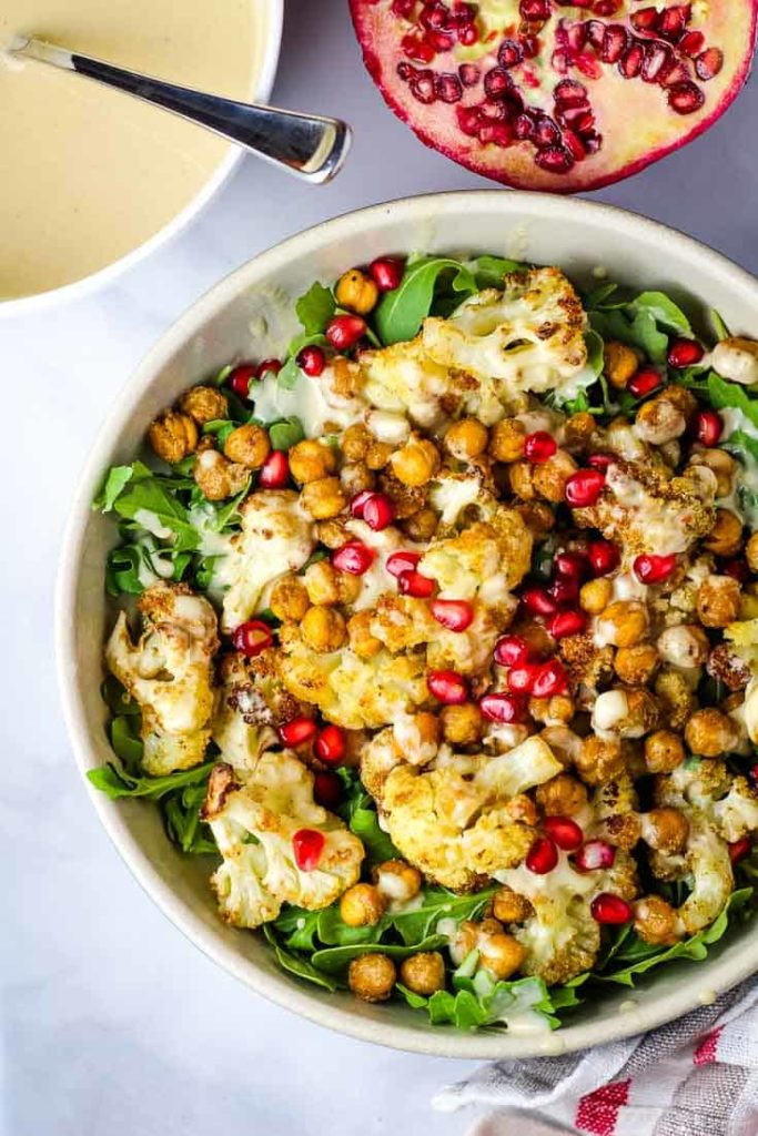 A bowl of roasted cauliflower salad with tahini dressing and a pomegranate half in background