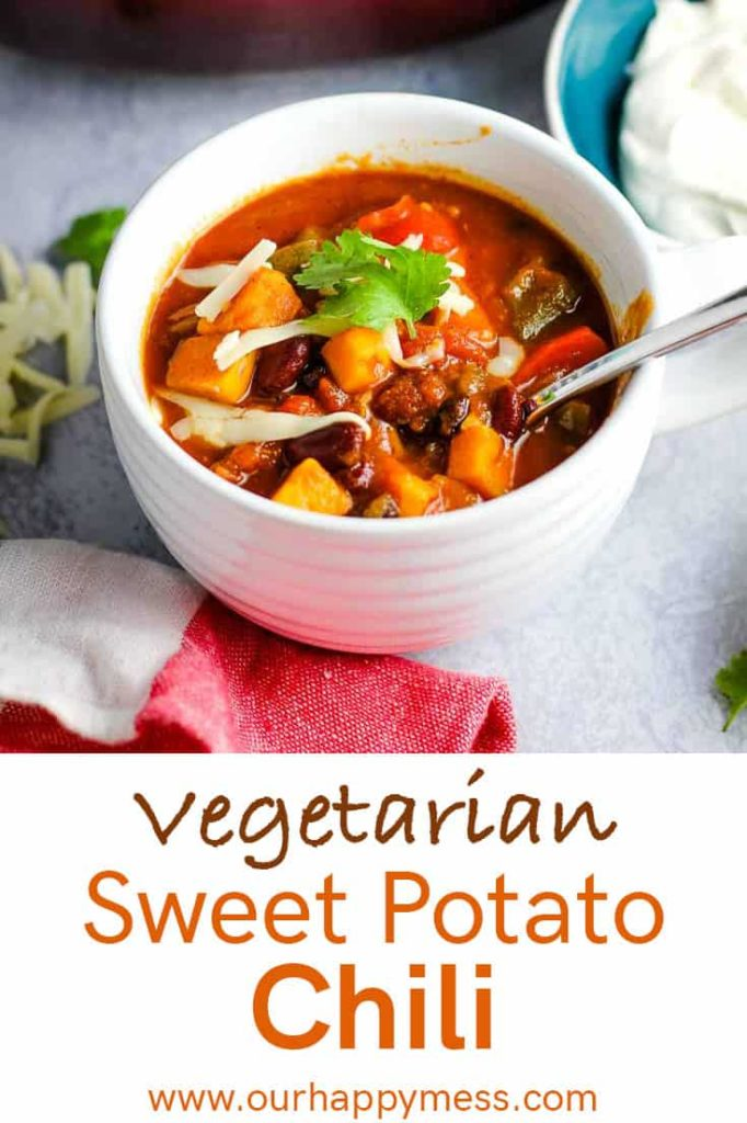 A bowl of vegetarian sweet potato chili topped with cheddar and cilantro