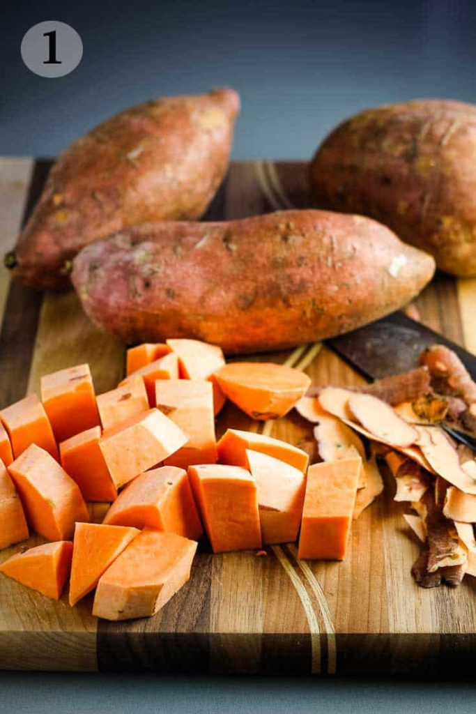 Sweet potatoes being peeled and cubed on a cutting board