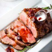 Sliced pork roast with orange cranberry sauce on a serving platter