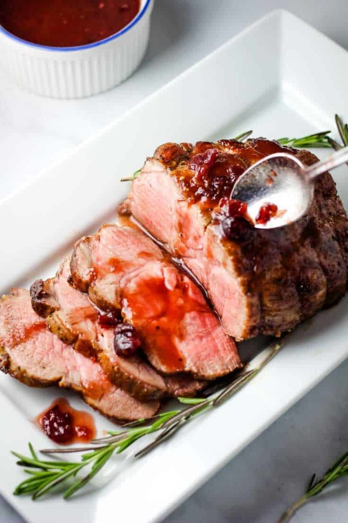 Sliced pork roast with orange cranberry sauce on a serving platter