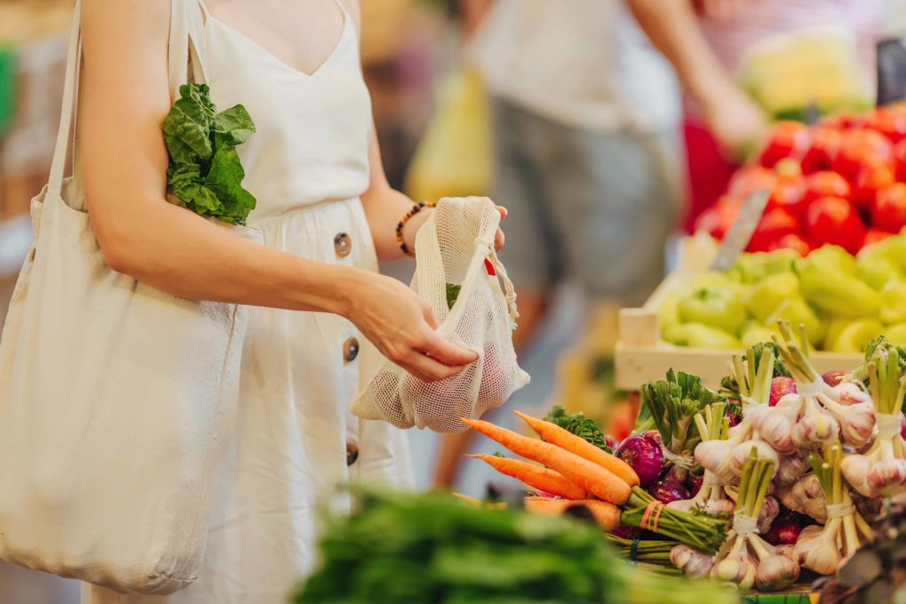 Woman picking produce and putting it into a reusable bag