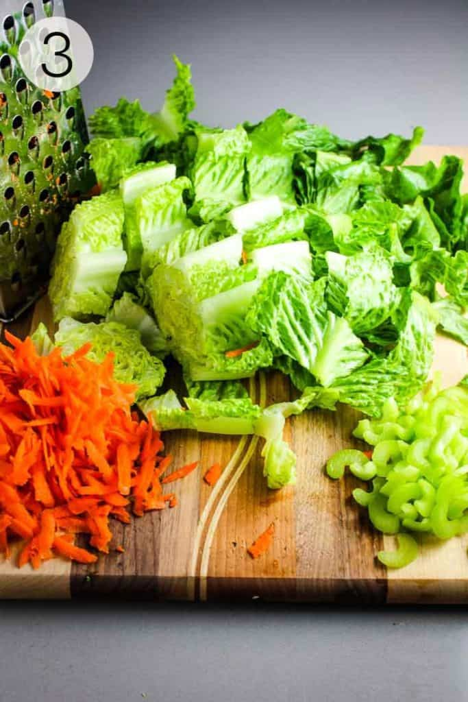 lettuce carrots and celery chopped on a cutting board