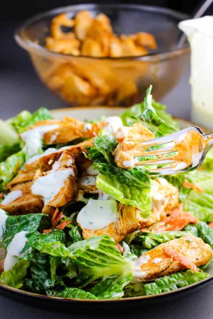 A bowl of buffalo chicken salad with ranch dressing
