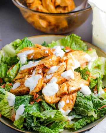 A bowl of buffalo chicken salad topped with ranch dressing