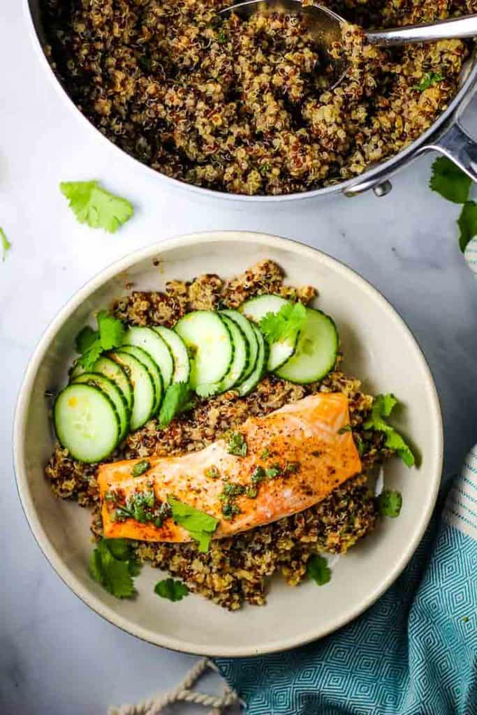 A roasted salmon fillet on a bed of quinoa with cucumber slices