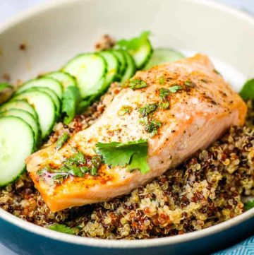 A roasted salmon filet on a bed of quinoa with cucumber slices
