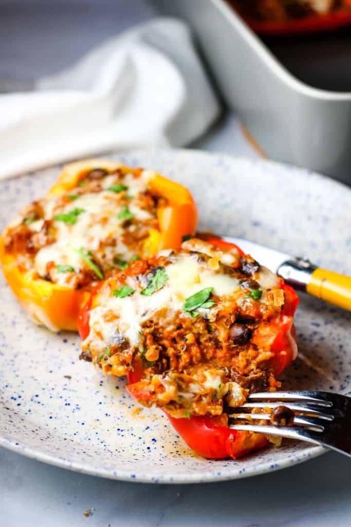 Two stuffed peppers on a dinner plate