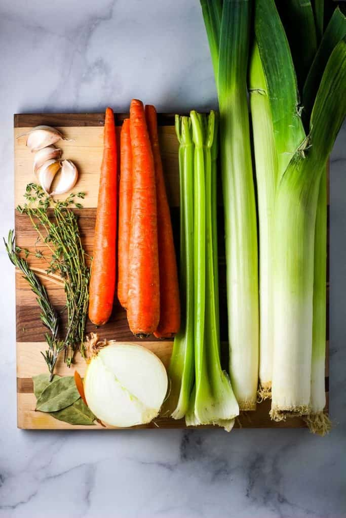 Carrots, leeks, celery, garlic and herbs unchopped, on a wooden cutting board