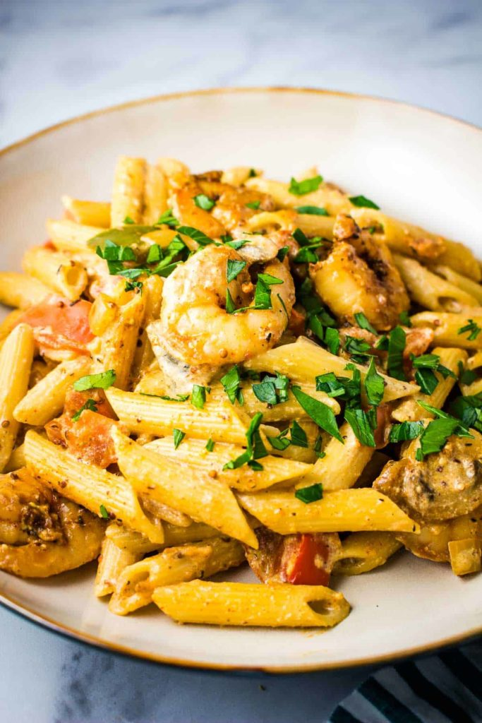 A bowl of Cajun shrimp pasta in a creamy sauce sprinkled with parsley