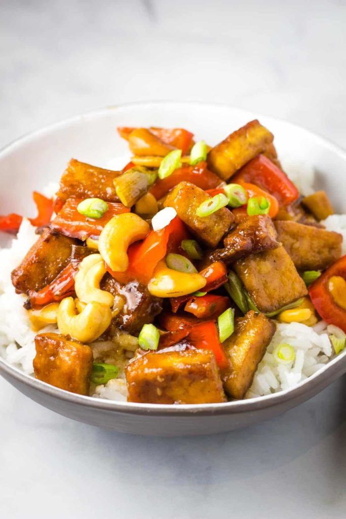A bowl of tofu stir fried with cashews over white rice