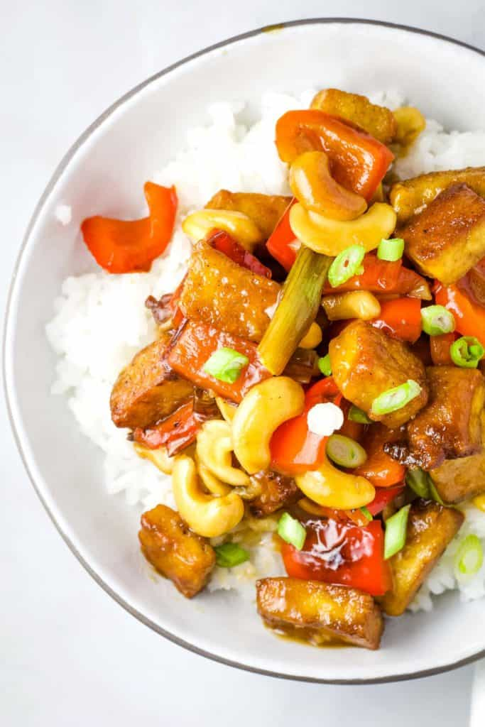 A bowl of kung pao tofu over white rice