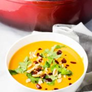 A bowl of sweet potato soup topped with cilantro, peanuts and sriracha