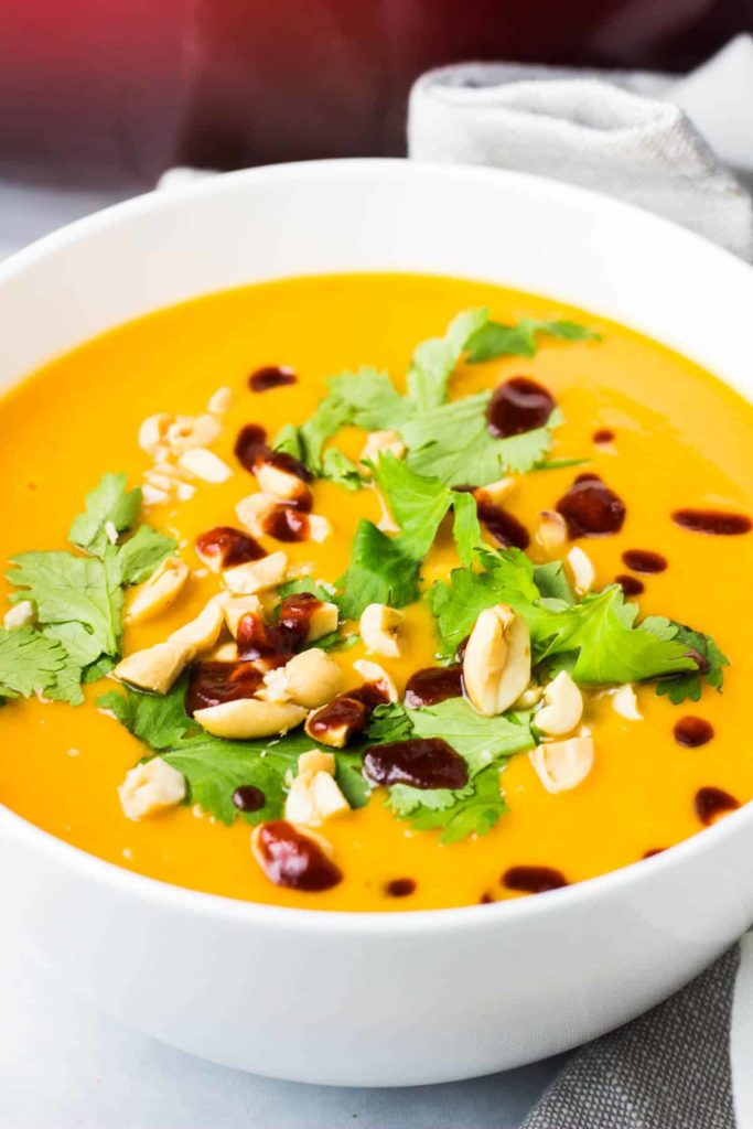 A bowl of sweet potato soup topped with cilantro, chopped peanuts and sriracha
