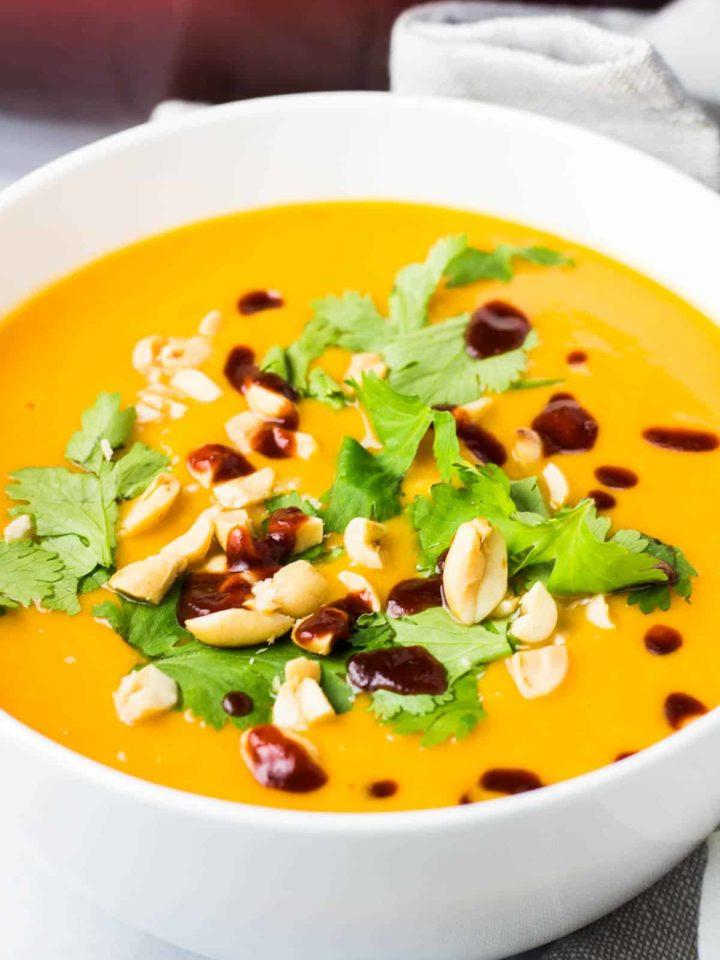 A bowl of sweet potato soup topped with cilantro, chopped peanuts and sriracha