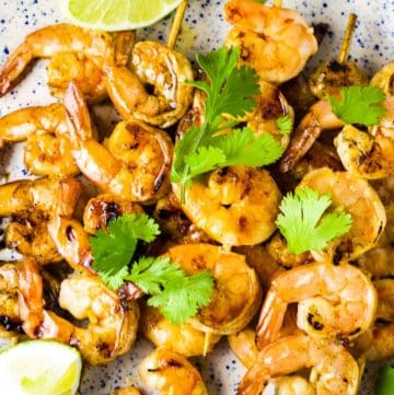Shrimp skewers on a platter with a garnish of lime wedges and cilantro