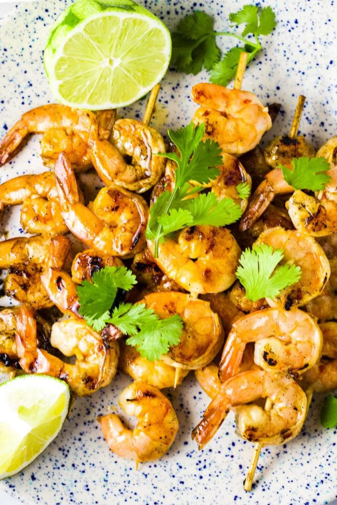 Chili lime shrimp skewers on a platter with a garnish of lime wedges and cilantro