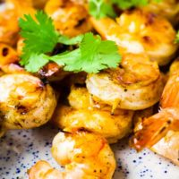 Shrimp on skewers piled onto a plate with a garnish of cilantro