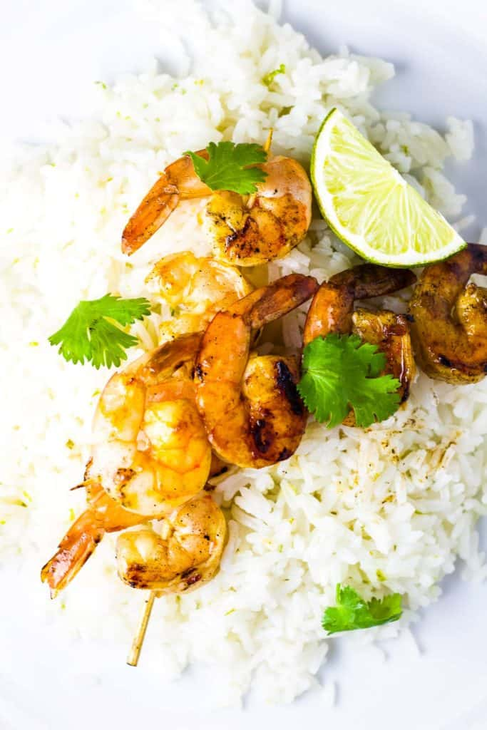 Two shrimp skewers over rice, garnished with cilantro
