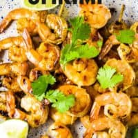 Shrimp skewers on a platter with a garnish of lime wedges and cilantro with text overlay