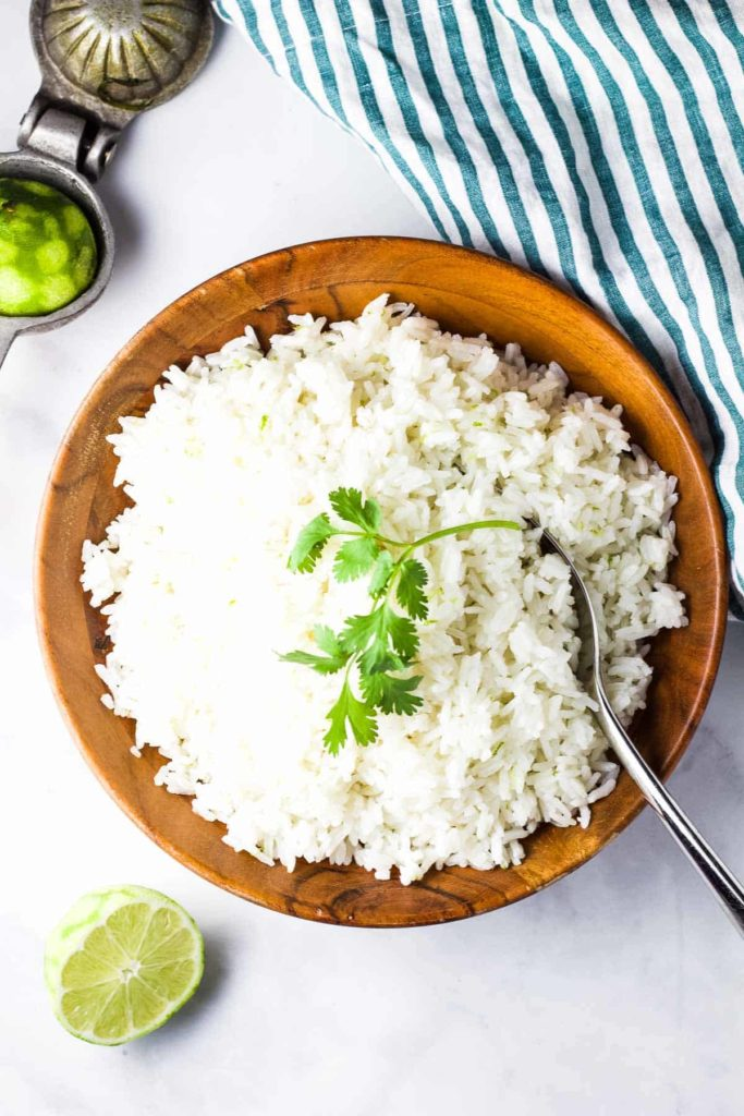 A large wooden bowl full of rice, garnished with a sprig of cilantro