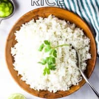 A large wooden bowl full of rice, garnished with a sprig of cilantro, with text overlay