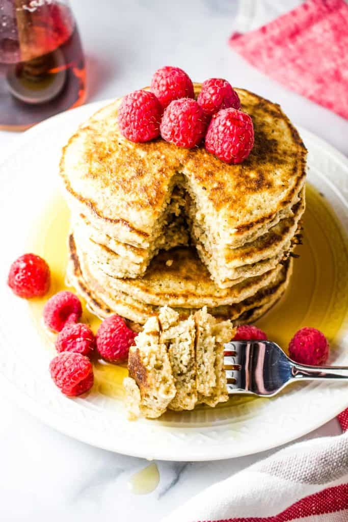 A stack of oat flour pancakes with raspberries and syrup with a wedge cut out and stuck on a fork