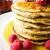 A stack of oat flour pancakes with maple syrup and raspberries on a white plate with text overlay